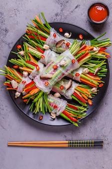 Involtini primavera con verdure e funghi shiitake su un piatto.