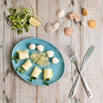 Involtini primavera con zucchine e mozzarella. alimento con i micro verdi sulla tavola di legno