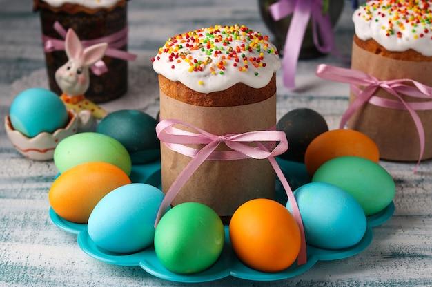 Natura morta di primavera di dolci pasquali e uova dipinte con bucaneve in background