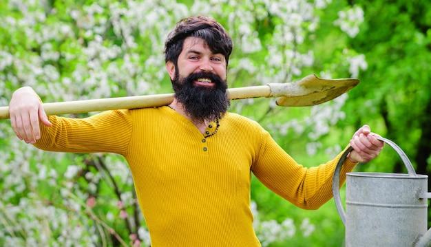 Tempo di primavera. giardiniere sorridente con annaffiatoio e vanga. irrigazione. lavoro in giardino.
