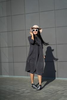 Collezione primavera alla moda. bella ragazza felice del brunette che porta vestito grigio alla moda e cappello alla moda. modello in abito alla moda in posa sul muro grigio