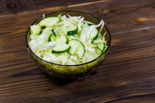 Insalata vegana di primavera con cavolo e cetriolo in una ciotola di vetro su un tavolo di legno