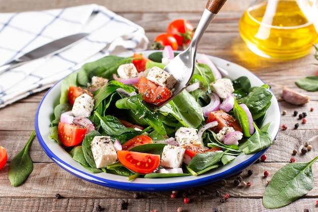 Insalata vegana primaverile con spinaci, pomodorini, spinaci baby, formaggio feta e cipolla rossa su un tavolo di legno rustico. concetto di cibo sano.