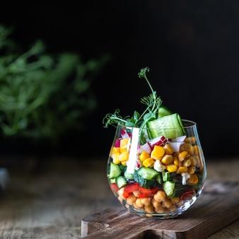 Insalata di verdure della primavera in una tazza di vetro su un fondo di legno. nutrizione appropriata. copia spazio. piazza. messa a fuoco selettiva.