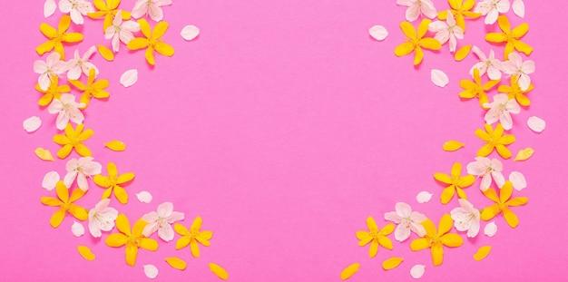 Fiori primaverili bianchi e gialli su sfondo di carta rosa