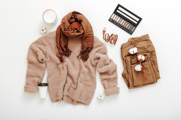 Abito donna autunno inverno primavera. abbigliamento femminile di base di moda set colori beige marrone maglione lavorato a maglia sciarpa e fiori di cotone cosmetici. vestiti piatti distesi su bianco.