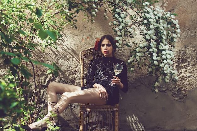 Donna di primavera. ragazza o donna graziosa, giovane modella alla moda con bicchiere di vino sotto i fiori che sbocciano nel cortile soleggiato all'aperto.