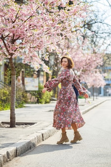 In primavera, una donna cammina lungo una strada fiorita con alberi di sakura. una ragazza con un lungo ed elegante abito vintage di seta cammina tra gli alberi in fiore