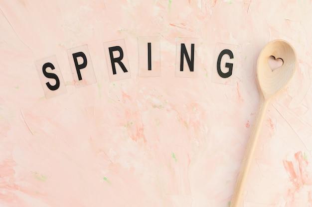 Parola primavera e cucchiaio mescolantesi su una rosa