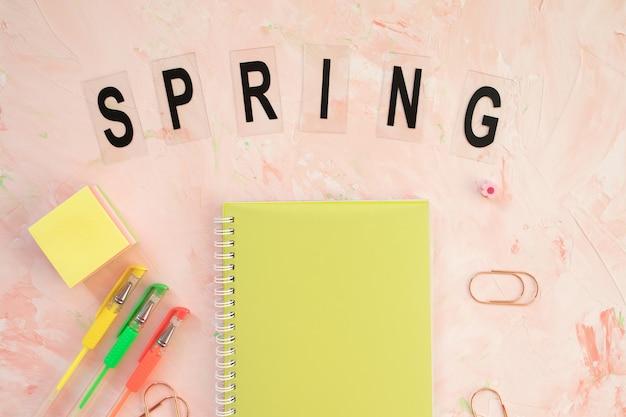 Parola di primavera e area di lavoro della scrivania dello studente con il taccuino e le penne sul rosa