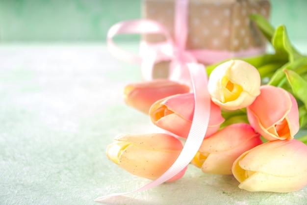 Bouquet di tulipani rosa di primavera con regalo per il giorno di san valentino, festa della mamma o concetto di pasqua. spazio della copia del fondo concreto verde chiaro