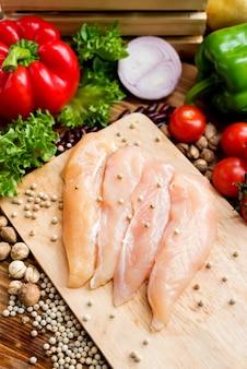 Cospargere il pepe nero sulla bistecca di pollo fresca con insalata. dieta di cucina e cibo sano.
