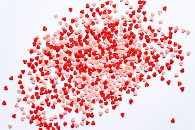 Spruzza la priorità bassa, lo zucchero spruzza i cuori rossi, la decorazione per torte e prodotti da forno. vista dall'alto, piatto. vacanze di san valentino.