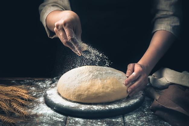 Cospargere la pasta cruda con la mano su uno sfondo nero.