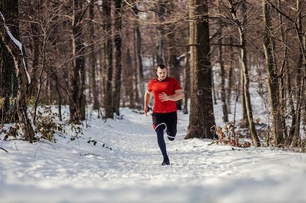 Velocista che corre veloce nei boschi sulla neve in inverno. stile di vita sano, sport invernali, sport all'aria aperta, abitudini sane