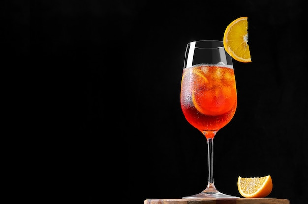 Spritz cocktail in bicchiere di vino con ghiaccio e fetta d'arancia su sfondo scuro