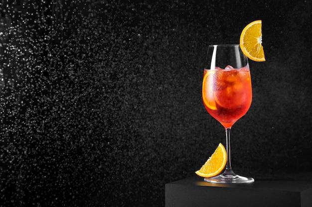 Spritz cocktail in bicchiere di vino con spruzzi d'acqua su sfondo scuro