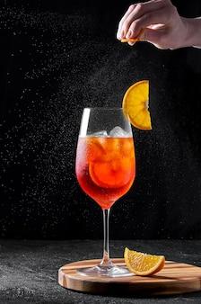 Spritz cocktail in bicchiere di vino su tavola di legno su sfondo scuro