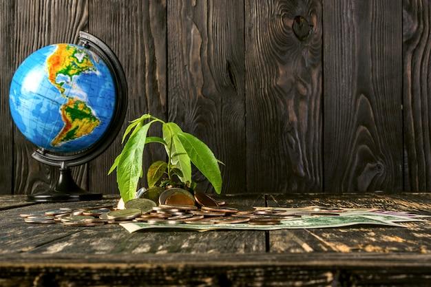 Il germoglio si alza da una pila di monete e banconote americane. e globo dal lato.