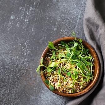 Germogli di semi diversi con foglia verde nella ciotola su grigio nero, vista dall'alto