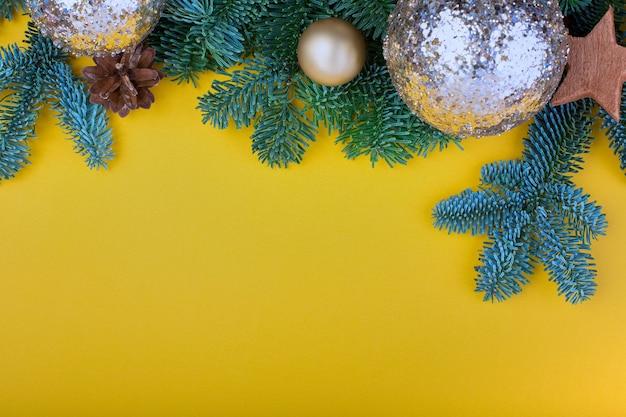 Ramo di abete, coni e decorazione di giocattoli vintage a natale o capodanno su sfondo giallo.