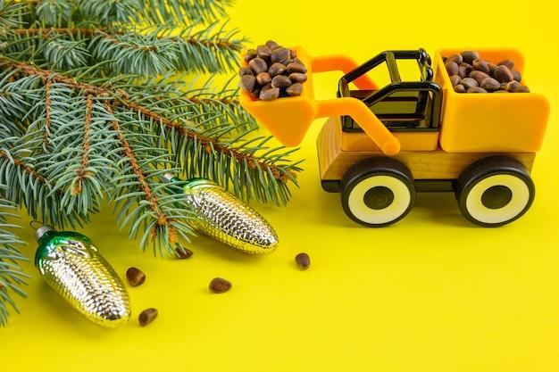 Rami di abete rosso, coni, noci e un escavatore giocattolo su uno sfondo giallo di capodanno.