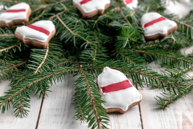Rami di abete rosso e biscotti a forma di anello campana con smalto rosso su fondo di legno bianco.