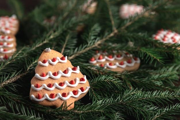 Rami di abete rosso, biscotti a forma di albero di natale su uno sfondo di legno scuro. concetto di celebrazione del nuovo anno con copia spazio