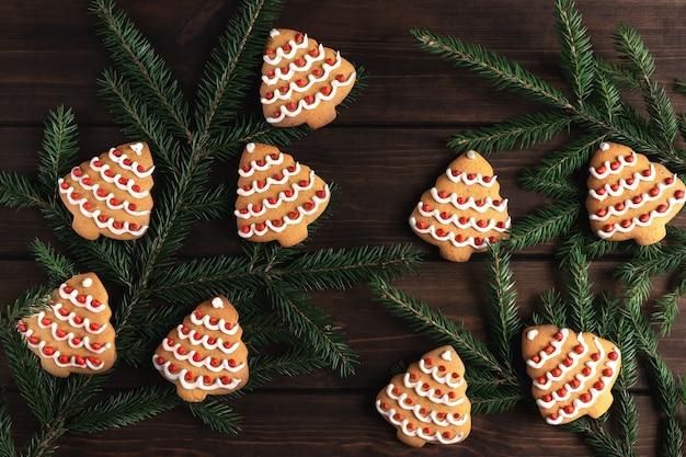 Rami di abete rosso e molti biscotti a forma di albero di natale su uno sfondo di legno scuro. concetto di celebrazione del nuovo anno con copia spazio