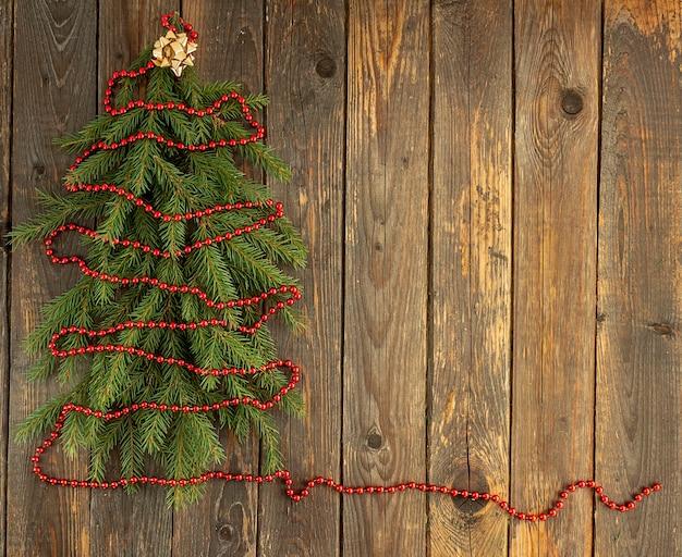 Abete rosso dai rami con perline rosse su fondo in legno. concetto di natale e capodanno. posto per il tuo testo.