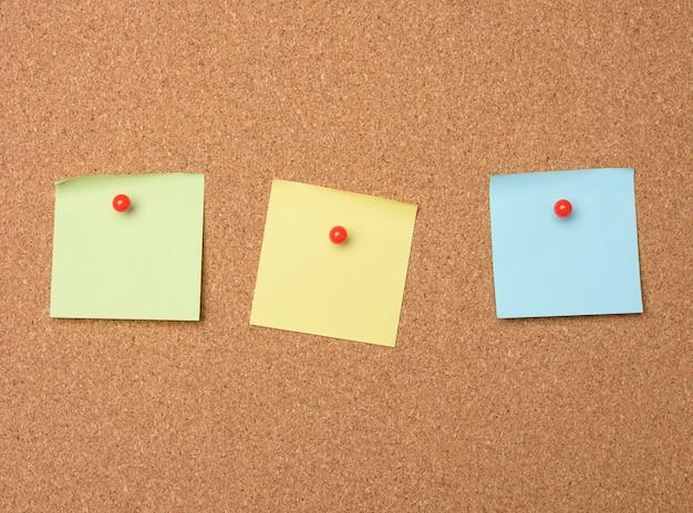 Pezzi di carta vuoti quadrati appuntati su una bacheca di sughero, copia dello spazio
