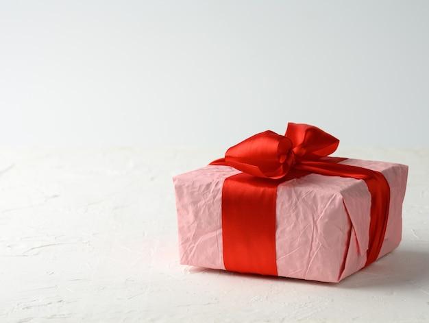 Scatola quadrata avvolta in carta rosa legata con nastro di seta rosso su sfondo bianco