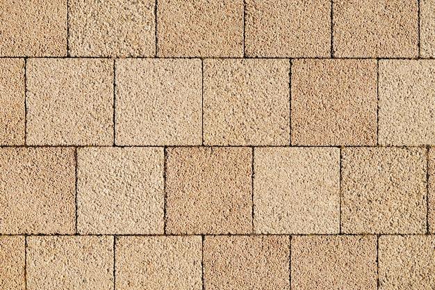 Percorso di mattoni quadrati in un parco. lastre di sabbia posate pavimentate per passerella. lastre per pavimentazione in calcestruzzo nel cortile o pavimentazione stradale. sfondo vista dall'alto strutturato.