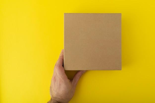 Scatola di cartone quadrata in mano su sfondo giallo.