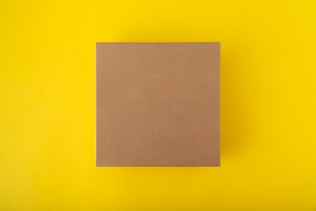 Scatola di cartone quadrata su sfondo giallo, vista dall'alto. scatola artigianale senza etichette.
