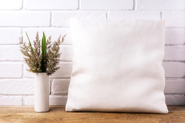 Mockup di cuscino quadrato in cotone con cordgrass e foglie verdi nel vaso