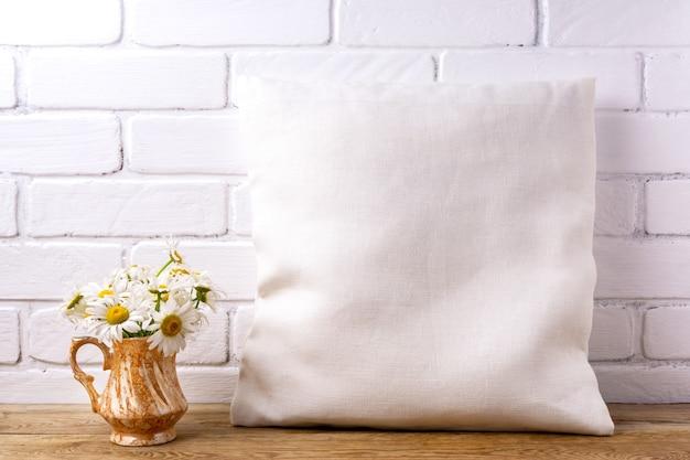 Mockup di cuscino quadrato in cotone con bouquet di margherite nel vaso dorato