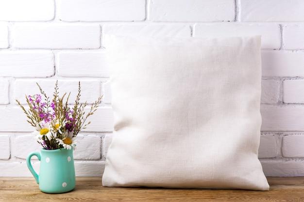 Mockup di cuscino quadrato in cotone con margherita e fiori di campo viola nel vaso della brocca di menta