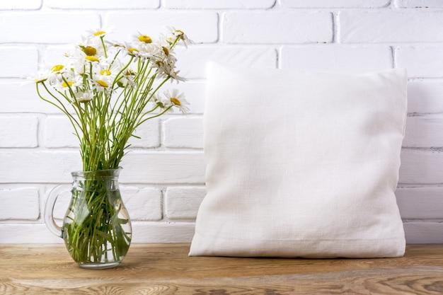 Mockup di cuscino quadrato in cotone con fiori di campo margherita in brocca di vetro
