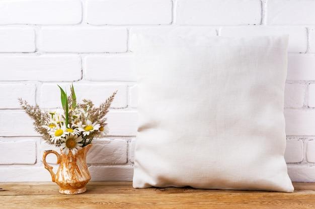 Mockup di cuscino quadrato in cotone con fiori di campo margherita ed erba nel vaso dorato