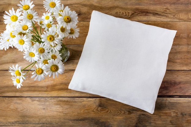 Mockup di cuscino quadrato in cotone con fiori di campo margherita