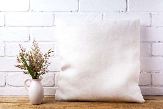 Mockup di cuscino quadrato in cotone con erba di ravenna nella brocca