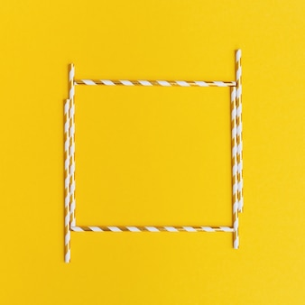 Cornice quadrata da cannucce di carta brillante con oro a strisce su sfondo giallo. cartolina d'auguri o invito di festa o celebrazione. creativo piatto disteso con spazio di copia.
