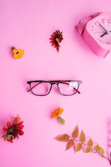 Occhiali quadrati, sveglia, foglie verdi su sfondo rosa pastello. concetto estivo, concetto minimale