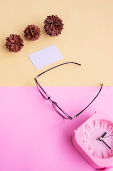 Occhiali quadrati, sveglia, fiori di pino su uno sfondo rosa pastello e giallo pastello. concetto estivo, concetto minimale