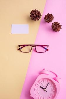 Occhiali quadrati su sfondo rosa e giallo con accessori aggiuntivi, sveglia e fiori di pino. stile estivo minimal