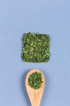 Quadrato fatto con polvere di prezzemolo, prezzemolo in cucchiaio di legno. un'opera d'arte in cucina