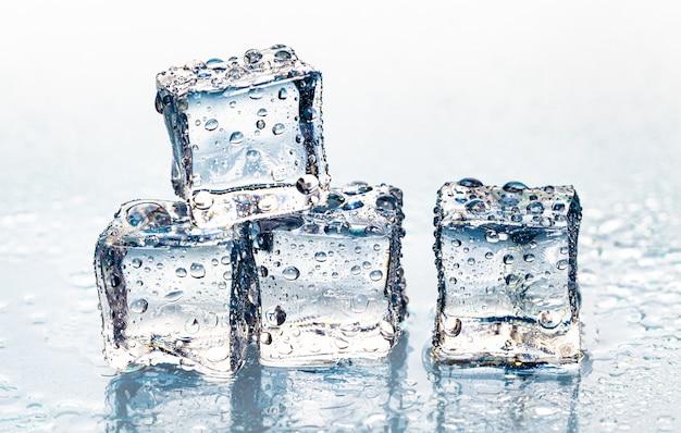 Cubetti di ghiaccio di fusione quadrati sulla tavola bagnata
