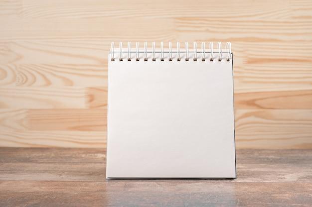 Taccuino quadrato con una pagina vuota sta in piedi sul tavolo di legno su uno sfondo di parete in legno.