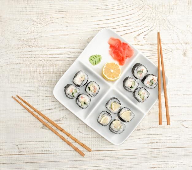 Piatto quadrato con rotoli su un tavolo di legno, zenzero, limone e wasabi. vista dall'alto